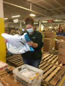 An eFulfillment Service employee is shown working in the warehouse, masked and reading the label on a package she's holding.