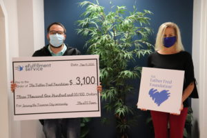 Mike Claycomb, eFS Warehouse Manager, stands on the right holding a large check representing the eFS donation to The Father Fred Foundation. To the right Elaine Talue, Advancement Manager of Father Fred, stands holding The Father Fred Foundation logo. Both are wearing face masks.