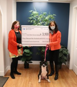 Two women stand on either side of a large check representing the donation eFS is making to the Great Lakes Humane Society. Patty Cake, the dog, is sitting in between them. Both humans are wearing face masks.