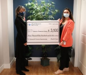 Two women stand on either side of a large check representing the donation eFS is making to the WRC. Both are wearing face masks.