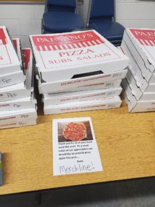 """A stack of pizza boxes is shown on a table with a paper sign in front of the boxes that reads, """"Thank you for all of your hard work this year! As a small token of our appreciation we would like to provide pizza again this year. Nate, Merchline!"""""""