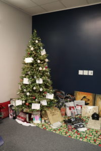 Image shows a decorated Christmas tree with a wide variety of gifts underneath.