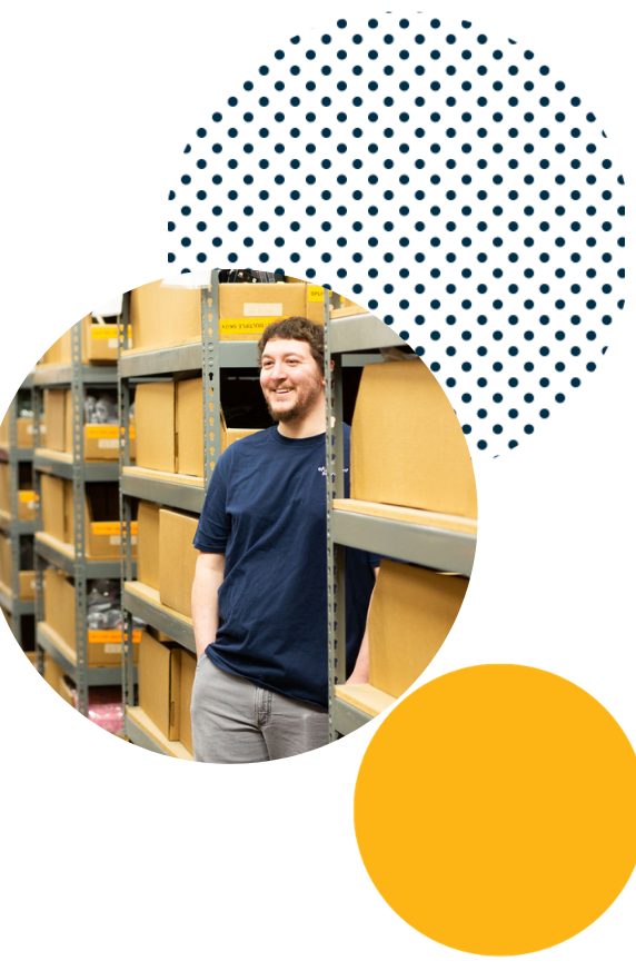 Efulfillment Service Employee Young Male Smiling From Between Racks