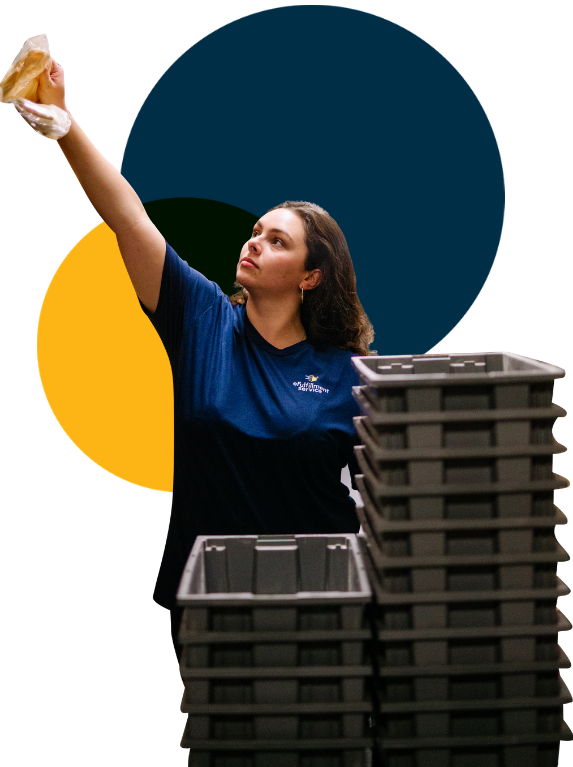 eFulfillment Service Female Employee Reaching up With Stacked Bins